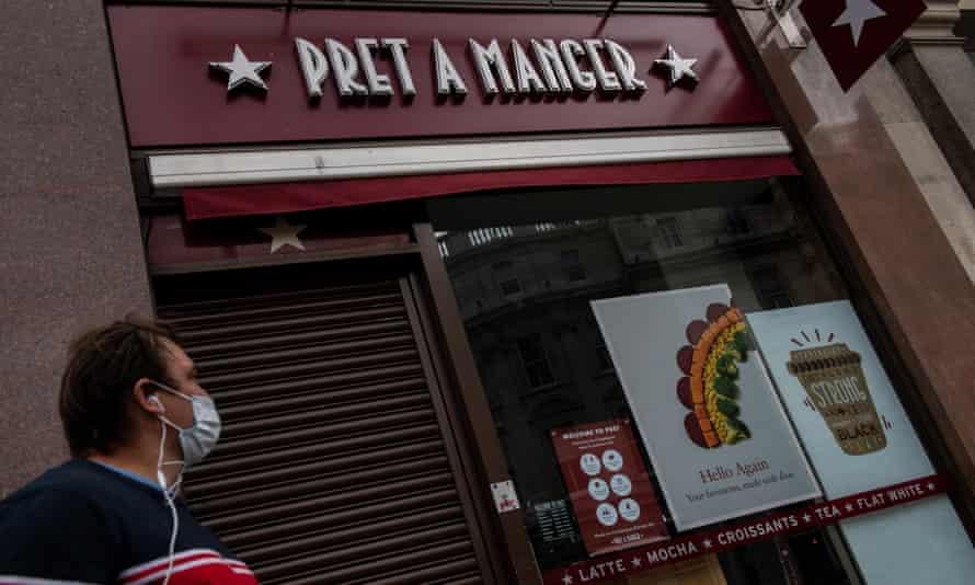 A man wearing a face mask walks past a closed Pret a Manger restaurant
