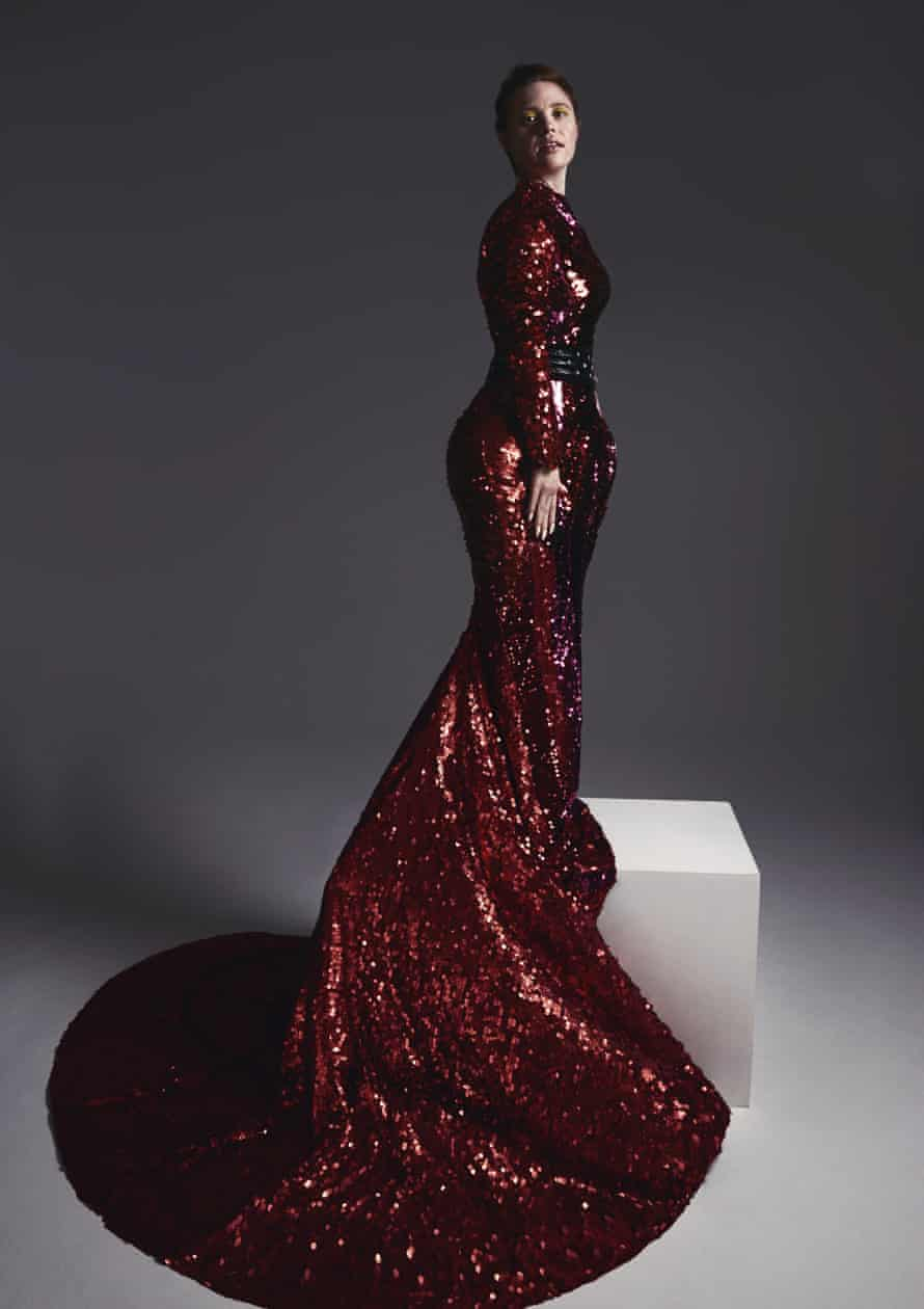 Sarah Gordy standing on a plinth in a tight-fitting long, deep red sparkly dress with a train swirling around the ground