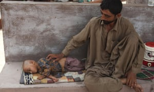 A man with his dehydrated daughter waits for a medical help outside a ward at a child hospital in Karachi on Wednesday.