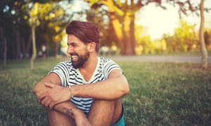 Portrait of laughing man in the park, sitting on the grass in summer day