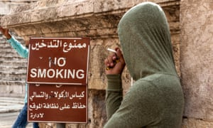 A man smoking in front of a 'no smoking' sign in Amman.