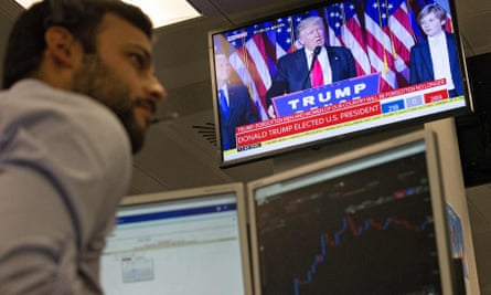 A trader works at his desk at ETX Capital in central London as the US presidential election result is announced on a TV screen.