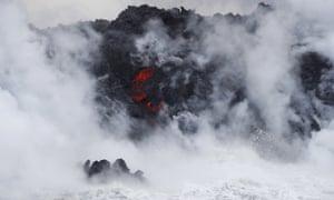 Steam rising as lava flows into the ocean near Pahoa, Hawaii