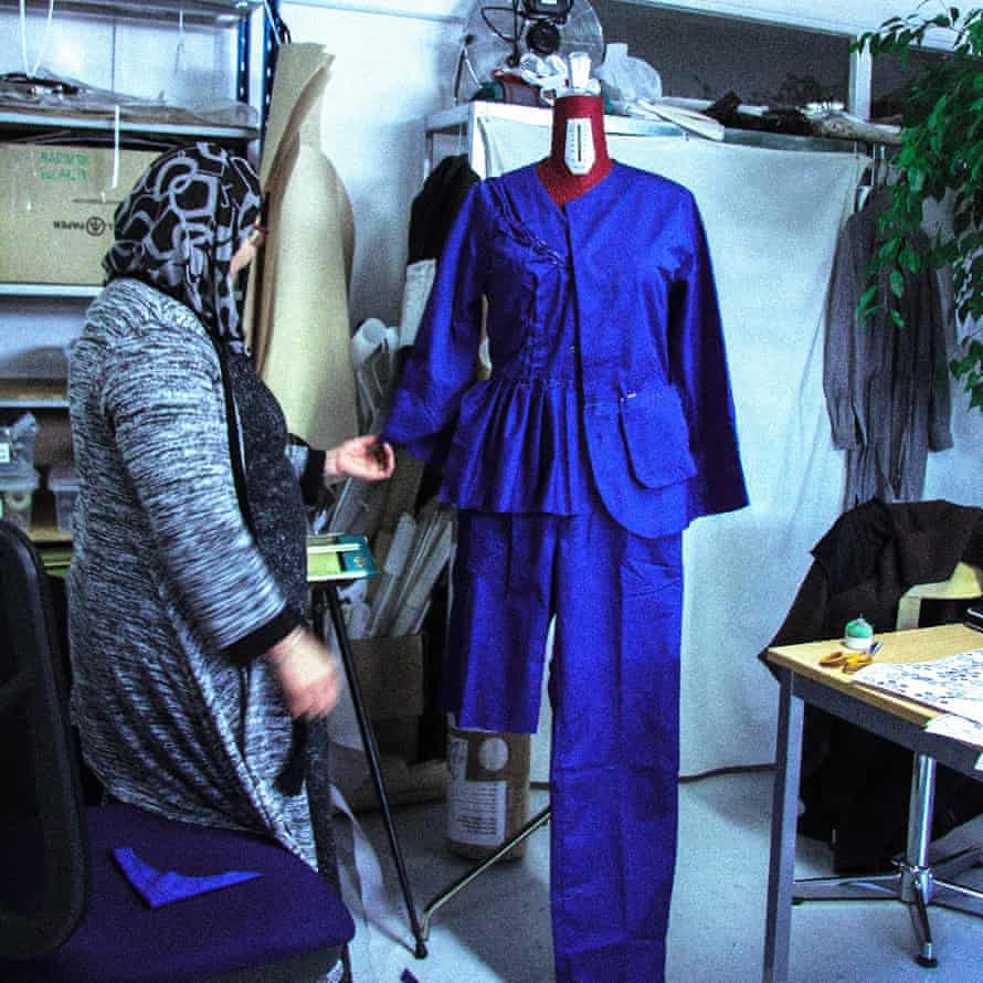 An employee in About A Worker's studio uses material from an old garment.