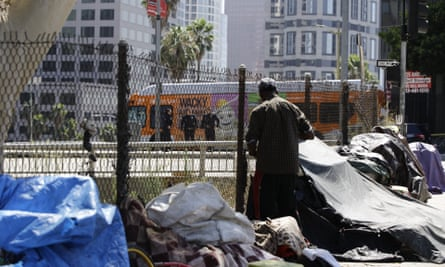 Los Angeles police officers guard a freeway ramp near a newly displaced homeless camp during Donald Trump's recent visit.