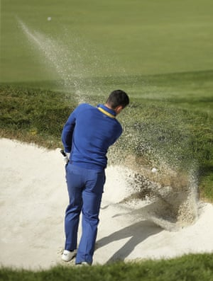 Rory McIlroy struggles to get out of a bunker on the 18th hole