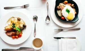 Two plates with a full cooked breakfast on a table set with knives and forks