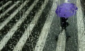 A woman is seen through a rain-streaked window walking along a road holding an umbrella