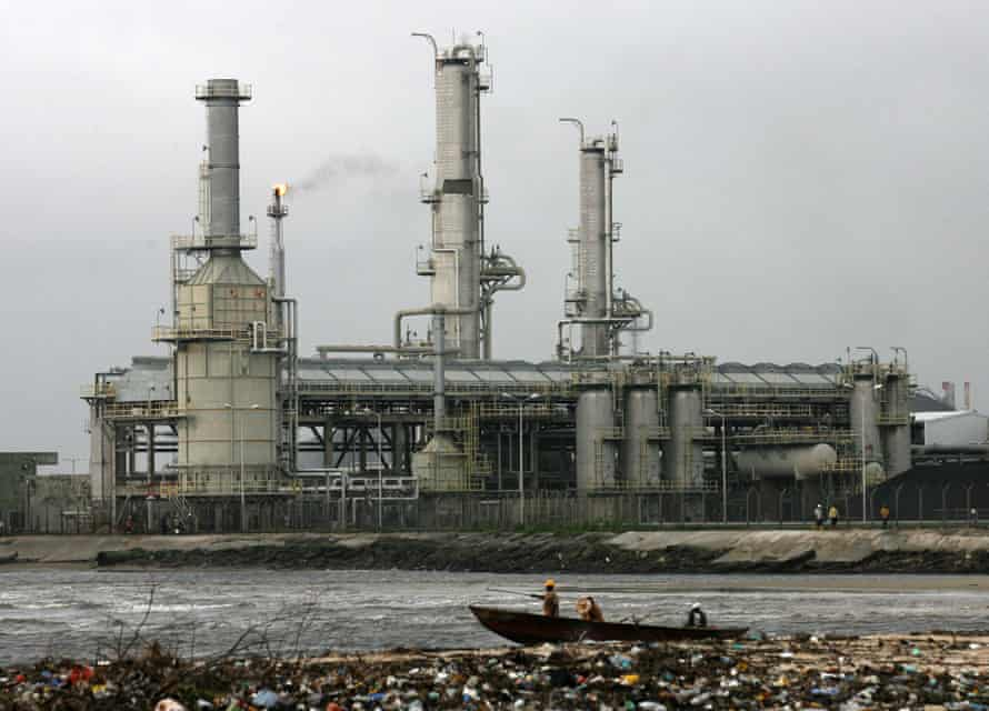 Local residents paddle a canoe past oil installations belonging to the Mobil oil company in Bonny Island, Nigeria.