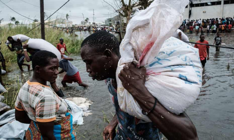 People take sacks of Chinese rice from a warehouse surrounded by water after Cyclone Idai hit in Beira, Mozambique.