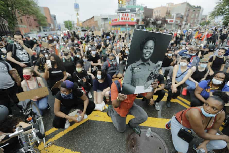 A man holds a photograph of Breonna Taylor on her birthday as he kneels with other protesters on Atlantic Avenue in Brooklyn.