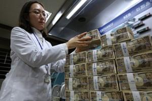 An employee stacks Japanese 10,000 yen banknotes in Seoul, South Korea