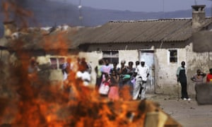 Residents in Naivasha, Kenya, watch a fire started during riots in 2008