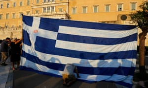 A protester kneels to pay his respect in front of a Greek flag.