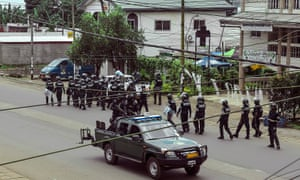 Cameroon police with riot equipment patrol a street in Buea.