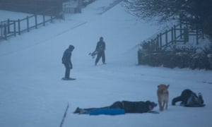 Young people in Cardiff use a road as a makeshift snowboarding slope on Thursday.