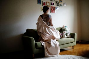 Rie Yoshihara shows off tattoos on her back at her home in Warabi, Saitama prefecture. Yoshihara, who works in a shop dressing tourists in kimonos, said her shocked father has still not seen her full back tattoo.