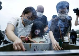 Family members burn incense sticks