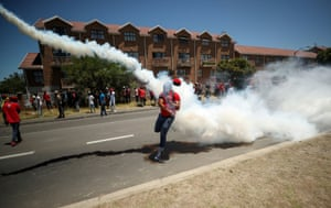 A protester throws a teargas canister back at police during an Economic Freedom Fighters party protest in Cape Town, South Africa