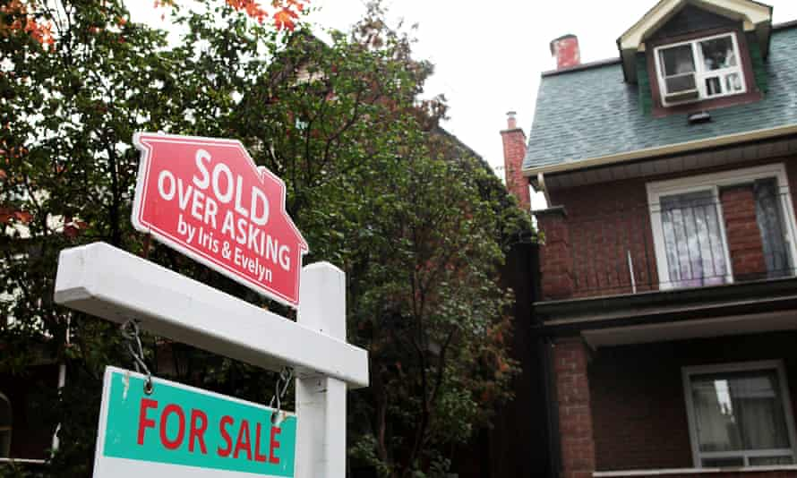 A 'Sold over asking' sign is on display on a house for sale in Toronto, Ontario.