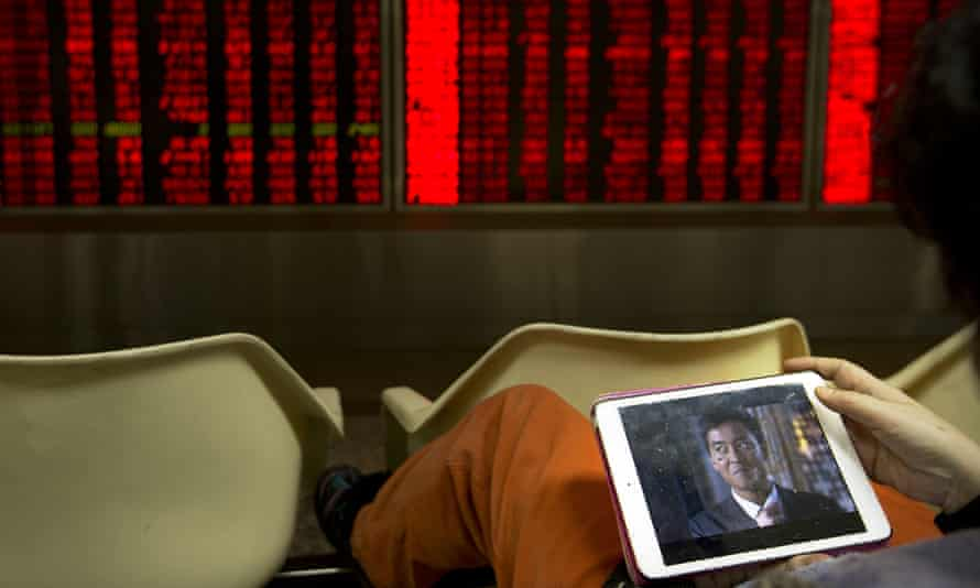 A Chinese investor monitors stock prices in a brokerage house in Beijing