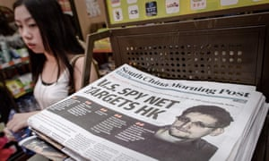 A woman walking past an edition of the South China Morning Post carrying the story of US intelligence whistleblower Edward Snowden (R) on its front page in Hong Kong.
