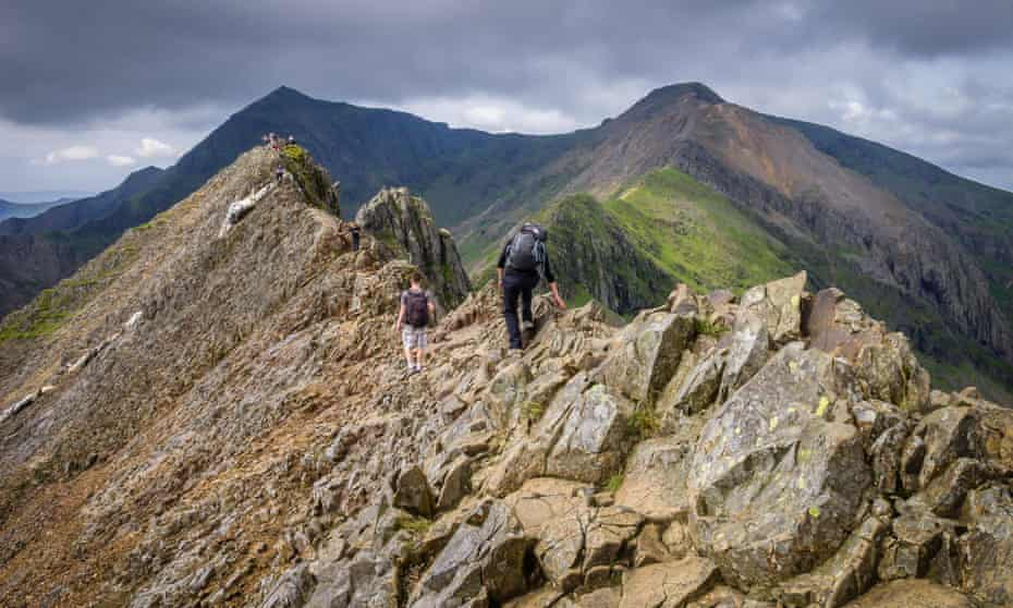An adult and child on a very steep mountain ridge; shadowy mountaintops are visible in the horizon; the sky contains dark clouds.