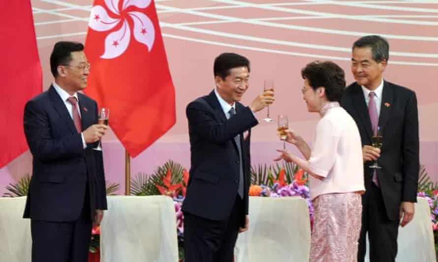 Carrie Lam and Luo Huining, clink champagne glasses at a ceremony celebrating the anniversary of the Hong Kong's handover.