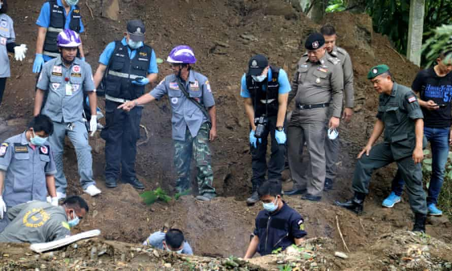 Thai Police and workers recover the bodies of a British citizen Alan Hogg and his Thai wife Nott Suddaen on their property in the country's north