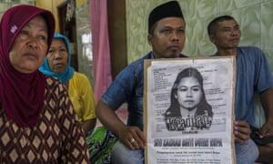 Family members of Indonesian maid Siti Zainab display a poster bearing her portrai. Siti Zainab was executed in April in Medina.