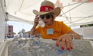 A volunteer, Jackie Rifkin, tries to keep cool at she works at a special Salvation Army hydration station in Phoenix.