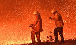 two firefighters facing flames and a shower of sparks