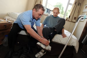 A care worker helps a brain-damaged man to dress himself in his own home.