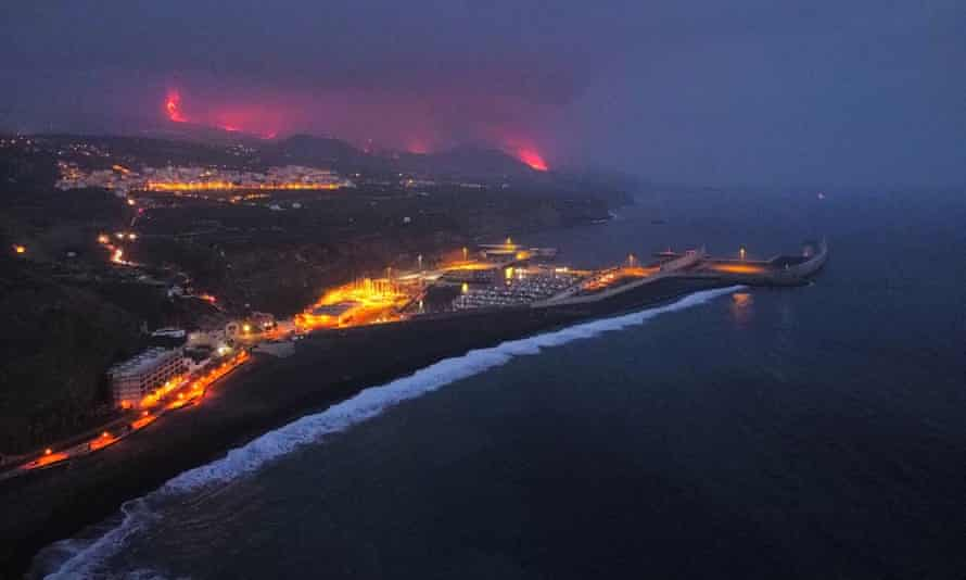 Lava is seen and smoke rises following the eruption of a volcano, in the Port of Tazacorte, on the Canary Island of La Palma