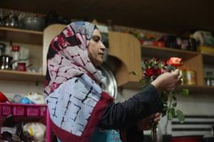 Nahla al-Zarda inspects roses inside her kitchen.