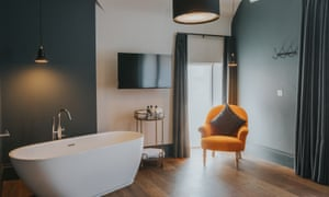 The egg-shaped bath in the corner of the bedroom with a mustard-yellow armchair.
