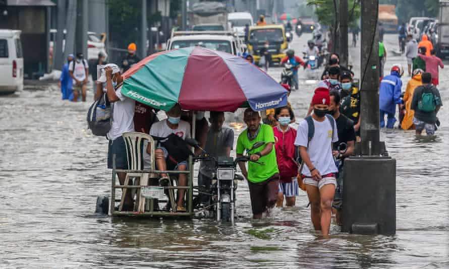 People wade through the flood water brought by heavy monsoon rains in Rizal province east of the Philippine capital Manila.