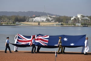 Defence personnel march with with the Australian flag during an Australia Day citizenship ceremony and flag-raising event in Canberra.