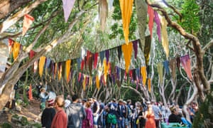 General view of festival goers dancing in the woods decorated with colourful bunting at Festival No 6 in Portmeirion, Wales.