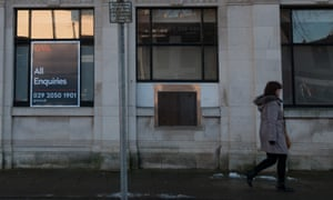 A woman walks past a closed bank branch in Wales