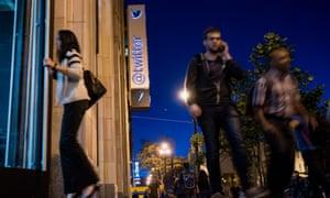 Pedestrians walk past Twitter headquarters in San Francisco, California on 21 October 2015.