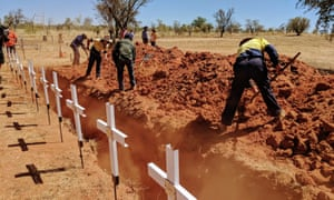 Local rangers start reburying the remains of more than 60 Aboriginal people whose graves were destroyed by floods
