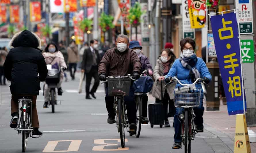 People cycle through a shopping street in Tokyo