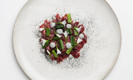 A round white plate with chopped beef and green leaves in the centre