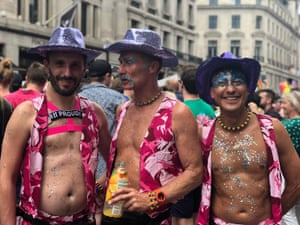 Three men wear matching floral outfits with plenty of belly on show.
