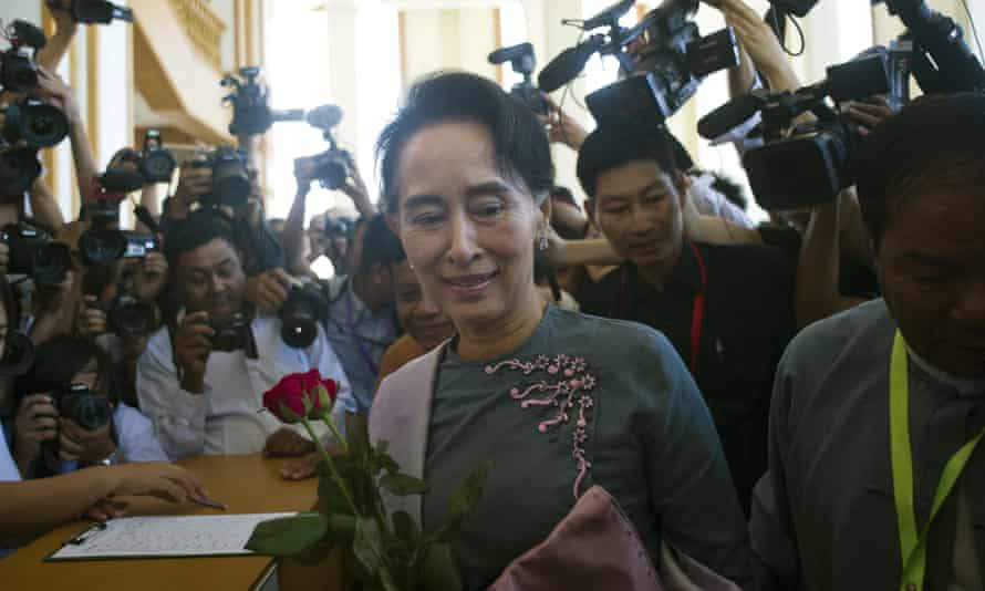 Aung San Suu Kyi accepts flowers from parliamentary staff as she arrives on Monday for Myanmar's first parliament meeting since the general elections.
