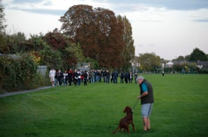 A small gaggle of away fans are escorted through a nearby park into the back entrance of the ground