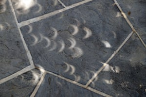 Projected images of the eclipse is seen through gaps in leaves on the sidewalk at the White House in Washington.