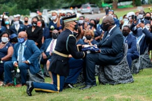 A member of the Honor Guard presents John-Miles Lewis, John Lewis' son, with the flag that shrouded his casket during the burial service of late Representative and Civil Rights leader John Lewis at the South-View cemetery in Atlanta.
