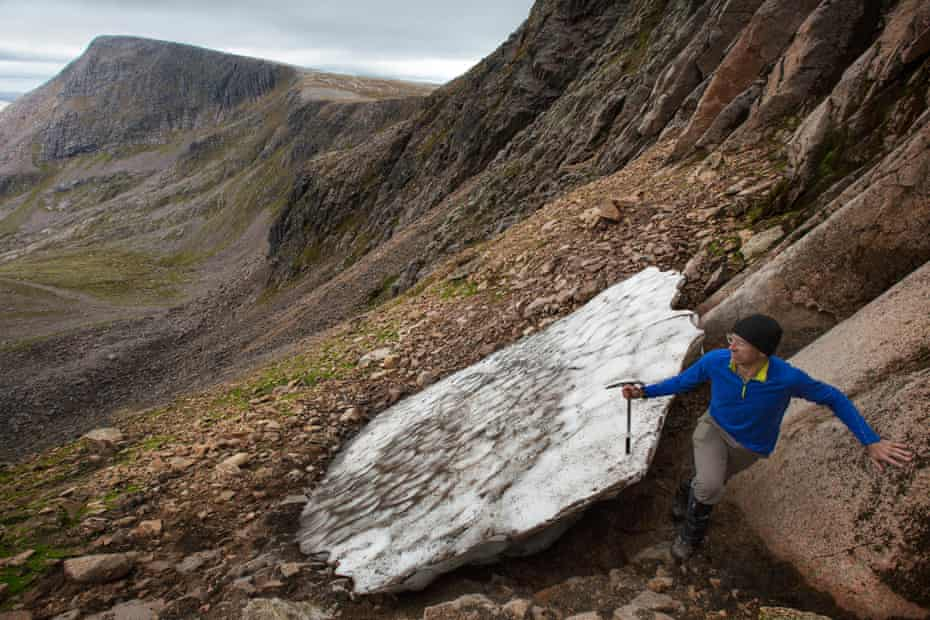 Cameron takes measurements of Sphinx snow patch as it melts away with Ben MacDui in the distance
